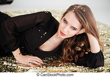 Relaxed gorgeous young woman with sequins on her hair -...