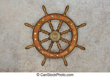 Vintage wooden ship steering wheel on a retro background -...