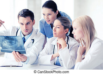 group of doctors looking at x-ray - healthcare, medical and...