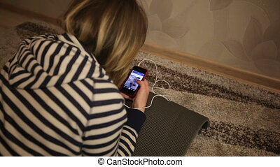 Pretty brunette texting with her smartphone at home in the living room