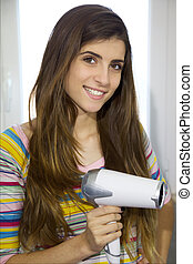 Cute girl with long hair holding blow dryer looking camera -...