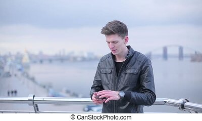 Man brunette makes photos of the city on smartphone