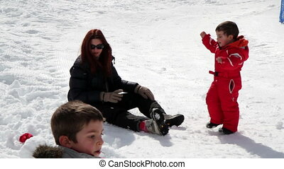 mum and two children playing with snowballs