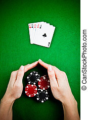 Female hands rakes up stack of gambling chips