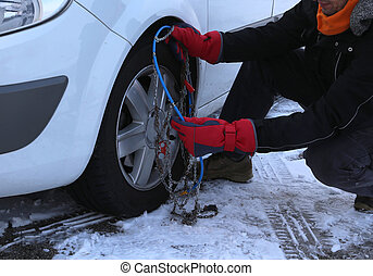 installing snow chains in the car tyre in winter on snow -...