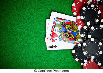 Black and red poker chips with cards in the background