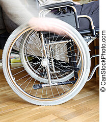 hand of the disabled man in the wheel of the wheelchair -...