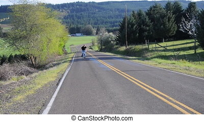Young adult riding bike on country