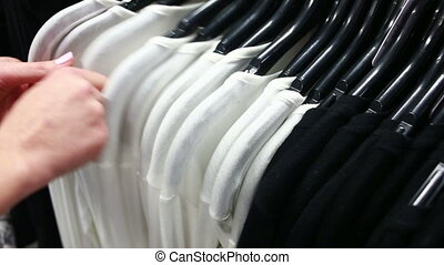 Buyer chooses a T-shirt in a boutique. rack