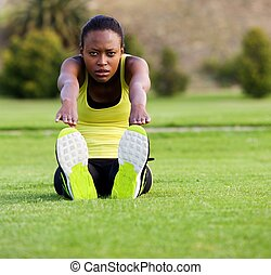Fit young woman stretching toe touch exercise  in the park