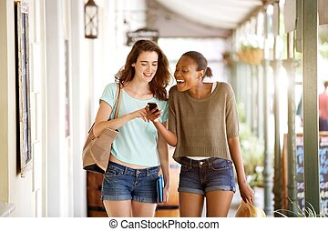 Smiling young women walking together using mobile phone