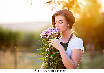 Young gardener in her garden smelling flowers, sunny nature...