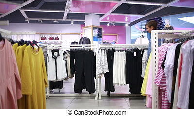 pretty elegant woman shopping in clothes store Hanger with...