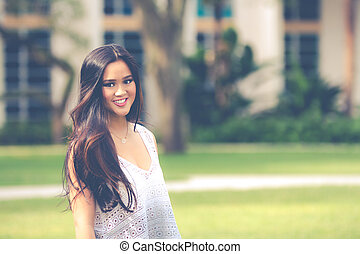 Portrait of a smiling young pretty Asian girl with long...