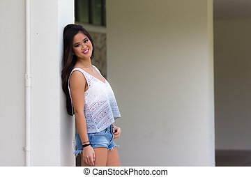 Portrait of a smiling young Asian woman in jeans shorts