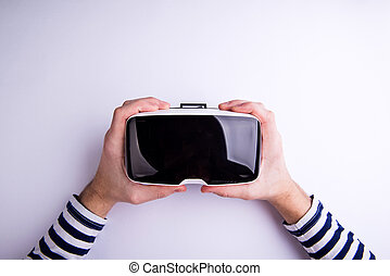 Hands of man holding virtual reality goggles. Flat lay....