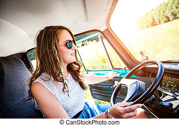 Hipster teenage girl inside an old campervan driving,...