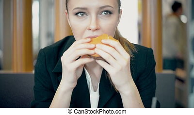 Woman eating burger and fries smiling. Beautiful mixed race   female model