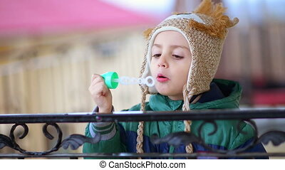 Kid Playing with Bubble Blower - Cute kid playing with a...