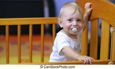 Cute baby laughing and showing his first teeth in a crib