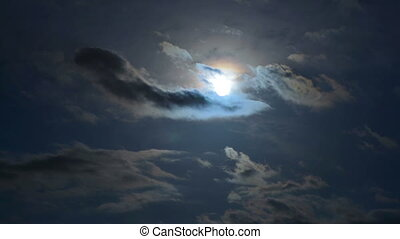 Moonscape in a cloudy day - Full moon surrounded by clouds...