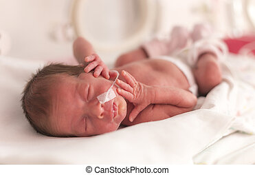 Premature newborn baby girl in the hospital incubator after...