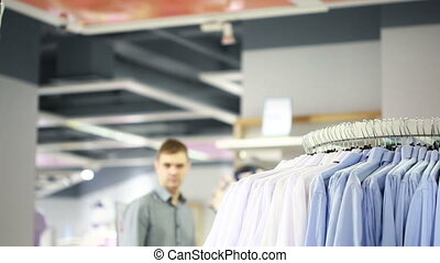 Portrait of a handsome young man shopping for clothes at...