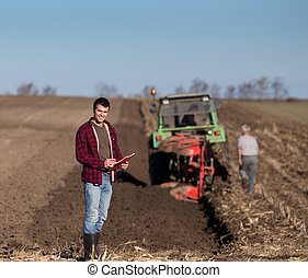 Farmer with tractor on field - Young handsome farmer...