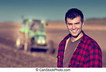 Farmer with tractor on field - Portrait of young handsome...
