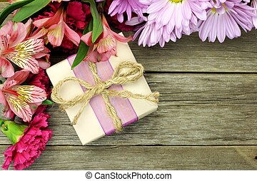 Rustic gift box with corner border of flowers on wood background