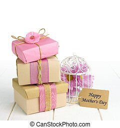 Stacked gift boxes with Happy Mothers Day tag and bird cage...