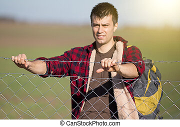 Man holding barbed wire fence - Young desperate man with...