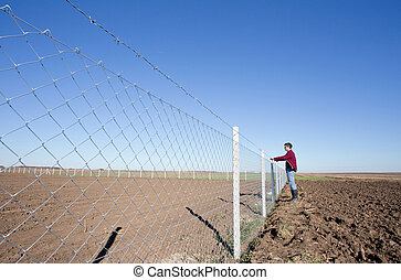 Man holding barbed wire fence - Young man holding barbed...