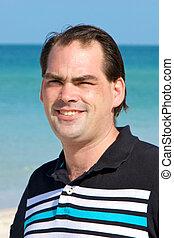 casual dark haired man at beach