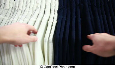 male customer looking for T-shirts in a fashion store -...