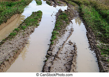 Dirt road with big puddles - Muddy water in a deep rut of...