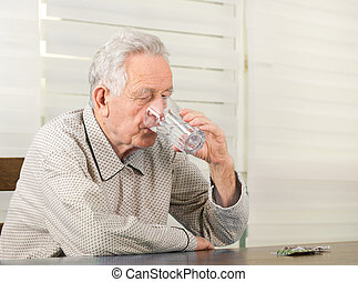 Old man taking medicals - Old man in pajamas drinking glass...