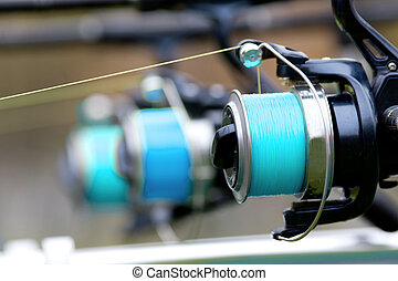 Fishing reels detail - Close up of three fishing rods...