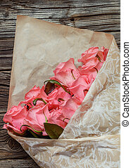 Bouquet of gift wrapped pink roses symbolic of love,...