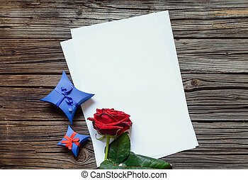 Papers on table with red rose and gift - Stacked blank...