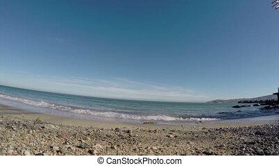 surf on stony beach, dolly camera move