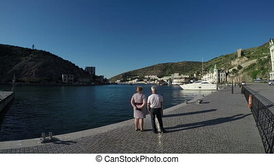 Mature man and woman looking at a bay in the resort