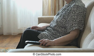 Woman switches channels of TV using remote control - Old...