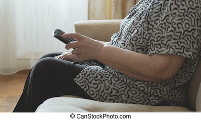Old woman holding a remote control - Old woman sits on the...