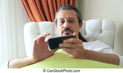 Man on the couch using smart phone - Middle aged, brunette...