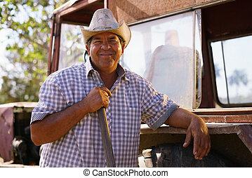 Portrait Happy Man Farmer Leaning On Tractor Looking At...