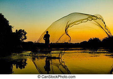 Fisherman with fishnet on the lake at sunset