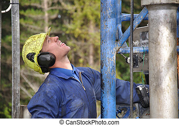 what's going on? - Drilling crewman looking up at the top of...