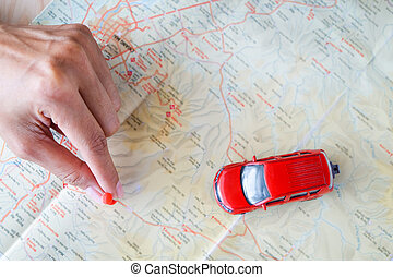 close up on a hand placing a pin on a map and car toy mark...