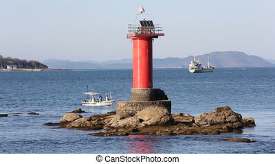 lighthouse with  fishing boat in the sea